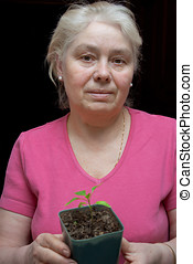 Woman holding a pot with seedling