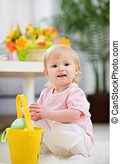 Baby gathering Easter eggs in basket