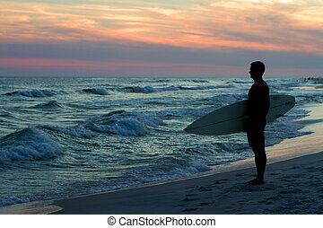 Surfer At Sunset - Surfer stands at the coastline holding...