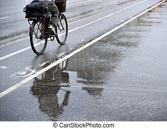 Cyclist in rain - Cyclist on bicycle path on rainy day....