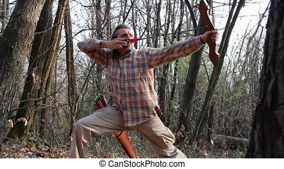 archery in the woods - man shooting with traditional bow in...