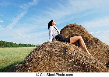 Woman on hay bale in summer field