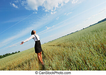 Attractive happy young woman in the field