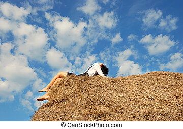 Young attractive woman on hay bale in summer field