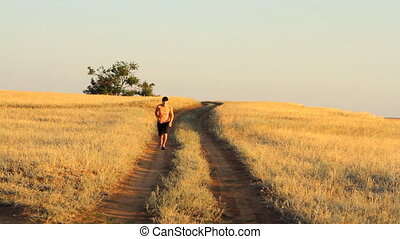 Girl walking on empty rural road far away in summer day