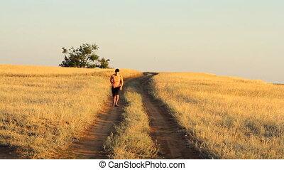 Girl walking on empty rural road far away in summer day