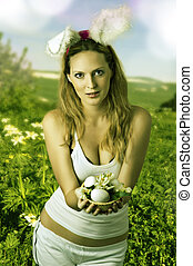 Sexy woman easter bunny on spring meadow with flowers