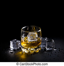 whiskey glass - glass of whiskey and ice over a black...
