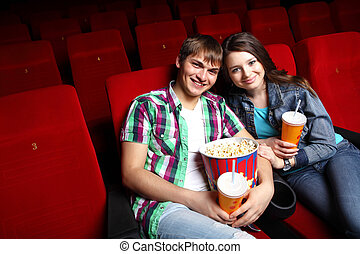 Young couple in cinema watching movie - Young couple sitting...