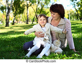 Grandmother with her little granddaghter in park -...