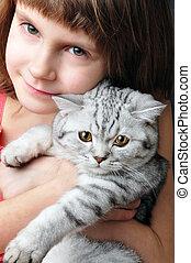 child hugging silver white cat kitten