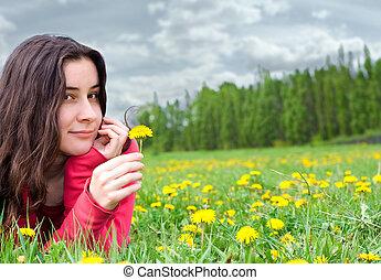 young dreaming girl lying among dandelions