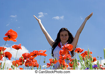 girl rising up her hands at poppy field