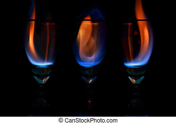 three goblets with blaze on black background - flame in...