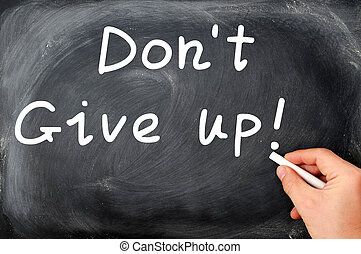 Dont give up written on a blackboard,with a hand holding...