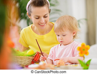 Mom helping baby painting on Easter eggs