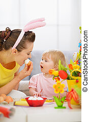 Mother and baby eating Easter egg