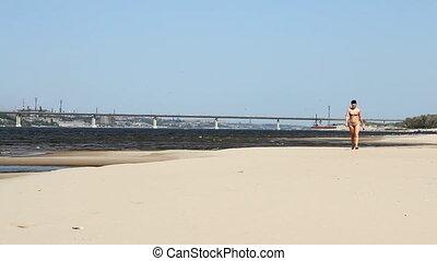 young woman in bikini barefoot running at the beach