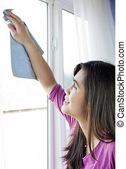 Teen girl or young woman cleaning windows inside home -...