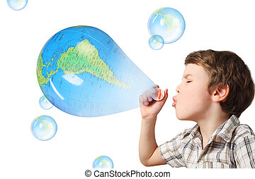 little caucasian boy blowing soap blue globe bubbles on...
