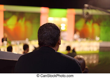 man sits in television studio and watches show on stage, behind