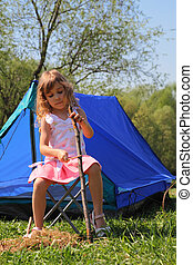 beautiful little girl in pink dress sitting near blue tent on nature