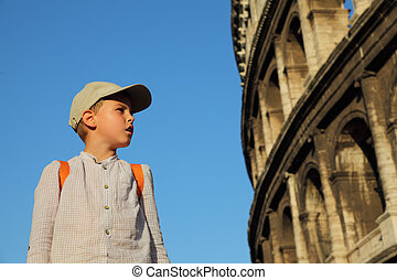 little boy in cap and backpack looks at old, stone walls of the Coliseum, blue sky