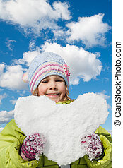 smiling little girl keeps in hands snow hearts on winter sky collage