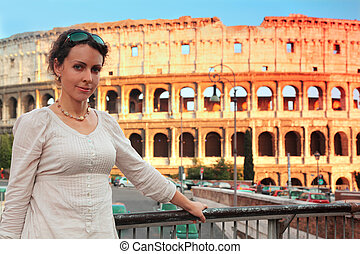 beautiful young woman in white wear standing on bridge near Colosseum at summer day