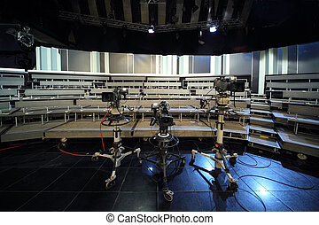 three professional black video cameras in television studio,...