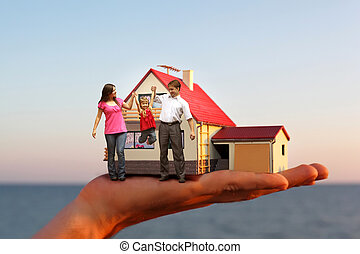 model of house with garage on hand against sea and family...