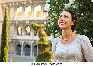 beautiful young woman stands near Colosseum and looks up,...