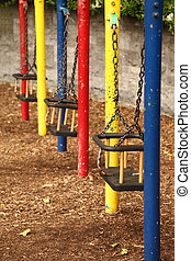 three empty teeter with chains, red, yellow, red, flaky paint