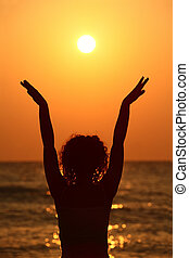 beautiful young woman standing on beach, watching sunset, raises her hands