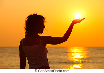 beautiful young woman standing on beach, watching sunset,...