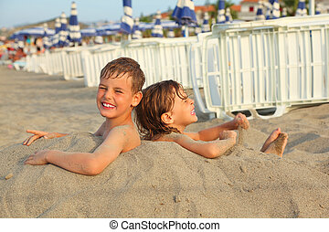 little brother and sister buried in sand on beach, rows of...