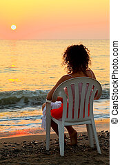 beautiful young woman sitting on white plastic chair on beach and watching sunset