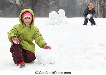 Two children play on outdoor in winter and sculpt snowman, focus on girl