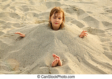 little girl after swimming is buried in sand on beach, a lot...