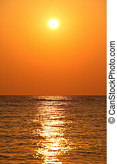 sun sets over horizon, sea, orange sunrsquo;s reflection in...