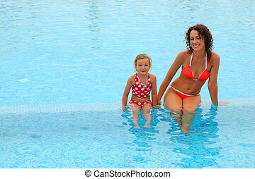 beautiful young mother in red bathing suit and her daugther...