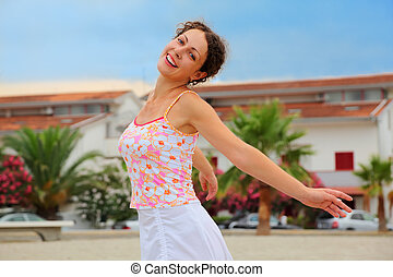 beautiful young woman in pink shirt spinning on beach and smiling