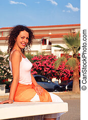 young beautiful woman sitting on white bench on beach, cars and building of sanatorium