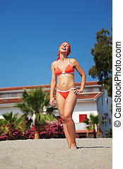 beautiful young woman in red swimsuit stands on beach and laughing