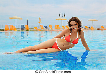 beautiful young woman in red bathing suit sitting in pool....