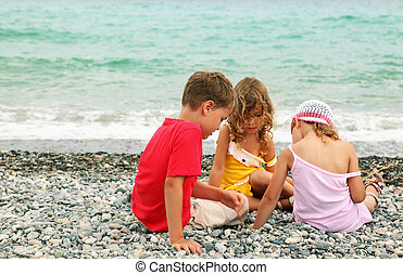 little brother and two sisters are sitting on beach and play. coast