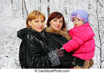 Grandmother, young mother and little daughter stand in woods...