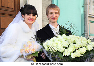 Smiling bride and groom with bouquets of roses stand near...
