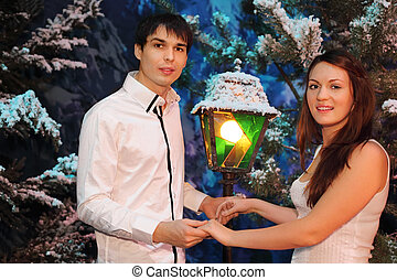 Young man and woman wearing white shirts stand near green trees in snow; broken lantern stands between people; focus on young man