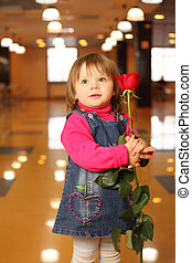 Little beautiful girl with red rose in hands stand in empty cafe
